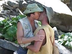 Gay fisherman kisses comrade by river